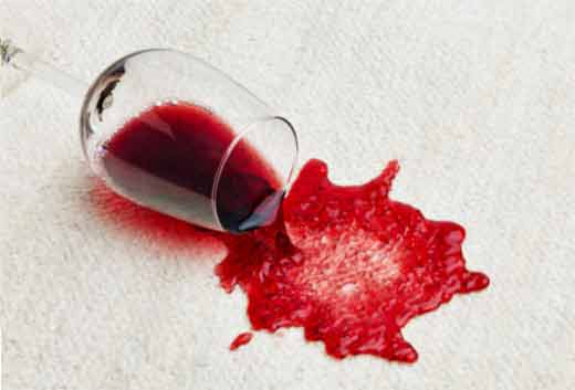 Picture showing a glass on wine fallig over on cream carpet